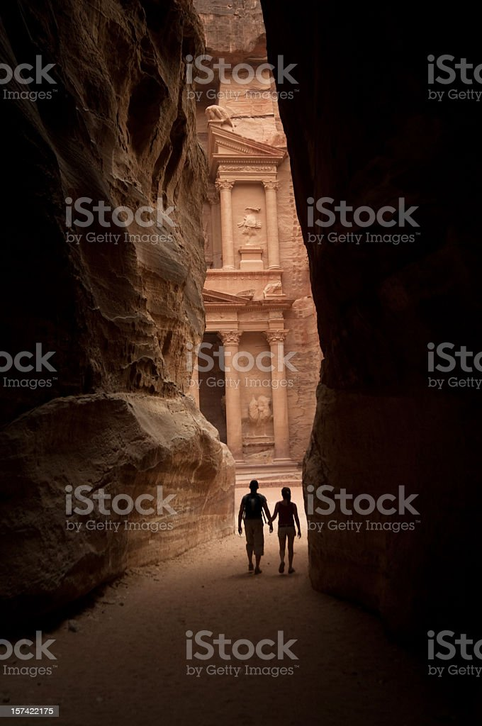 Two figures approach the lost city of Petra stock photo