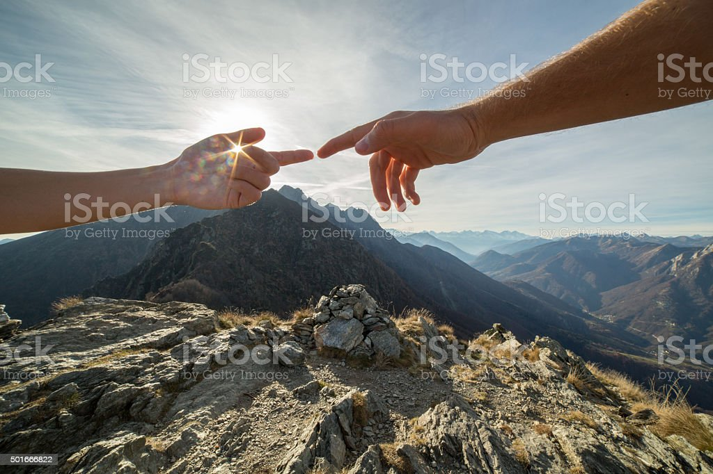 Two fingers touching in nature, mountain lake landscape stock photo