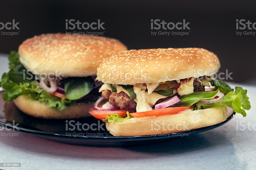Two finished hamburgers on the plate. Cooking burger concept stock photo