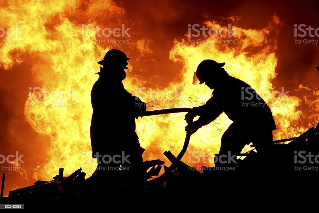 Two fire fighters and flames stock photo