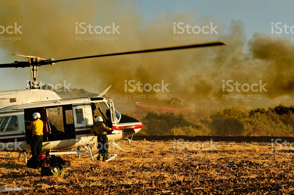 Two firefighters at helicopter in front of forest fire stock photo