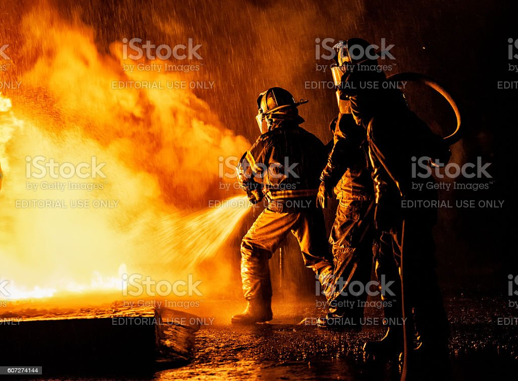 Two firefighters fighting a fire with a hose and water stock photo