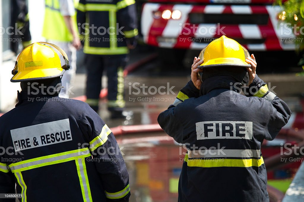 Two firefighters in black and neon yellow uniform stock photo