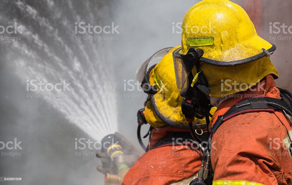 two firemen in helmet and oxygen mask spraying water stock photo