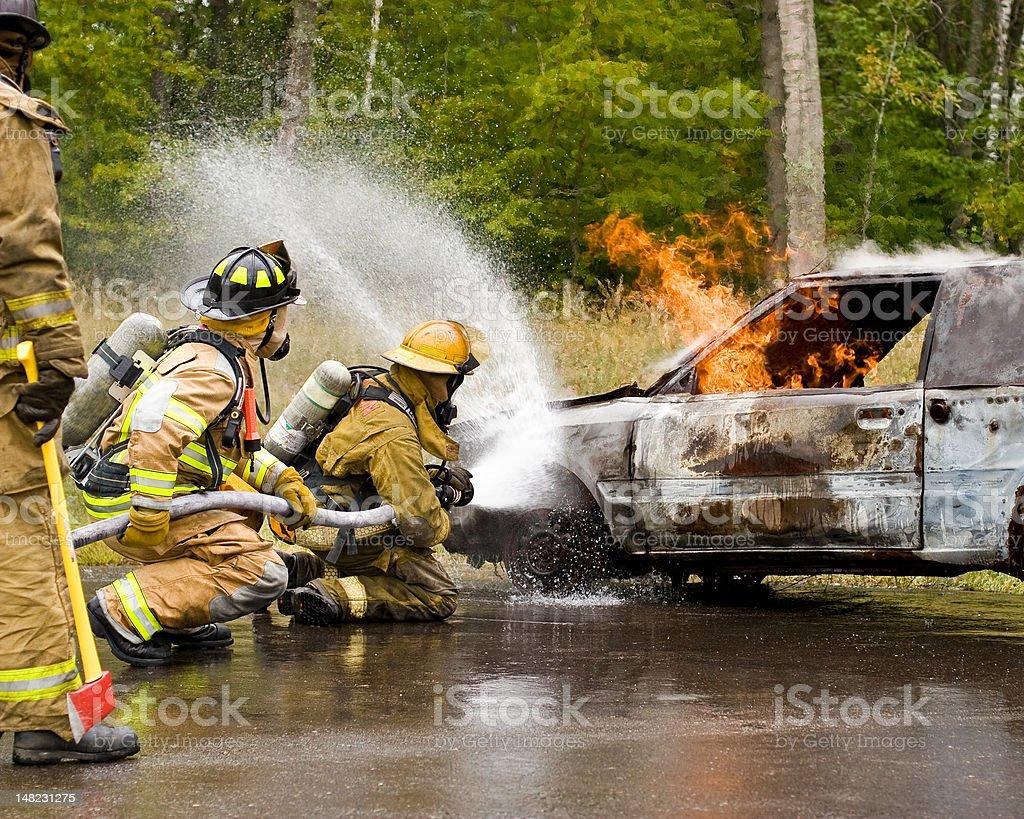 Two firemen spraying a burning car. stock photo