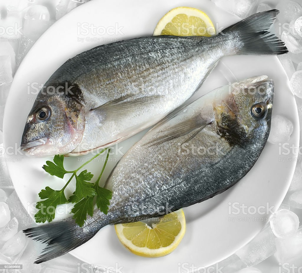 Two fish on a plate with lemons royalty-free stock photo