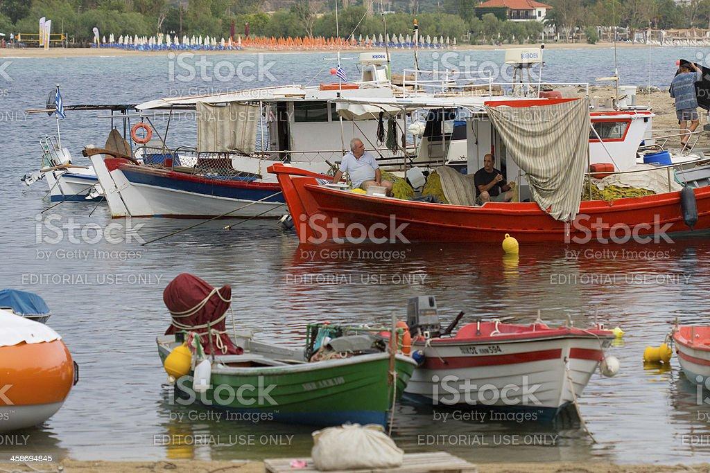 Two fisherman talking and repairing net stock photo