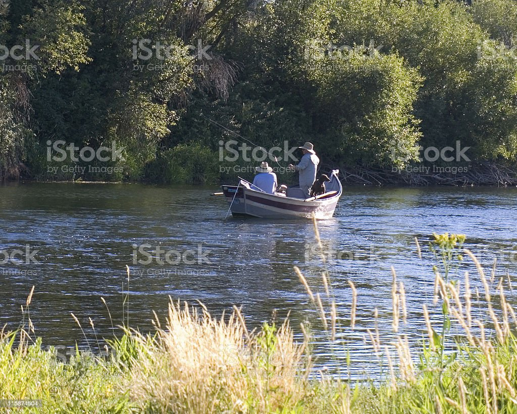 Two fishermen and a dog in fishing boat stock photo