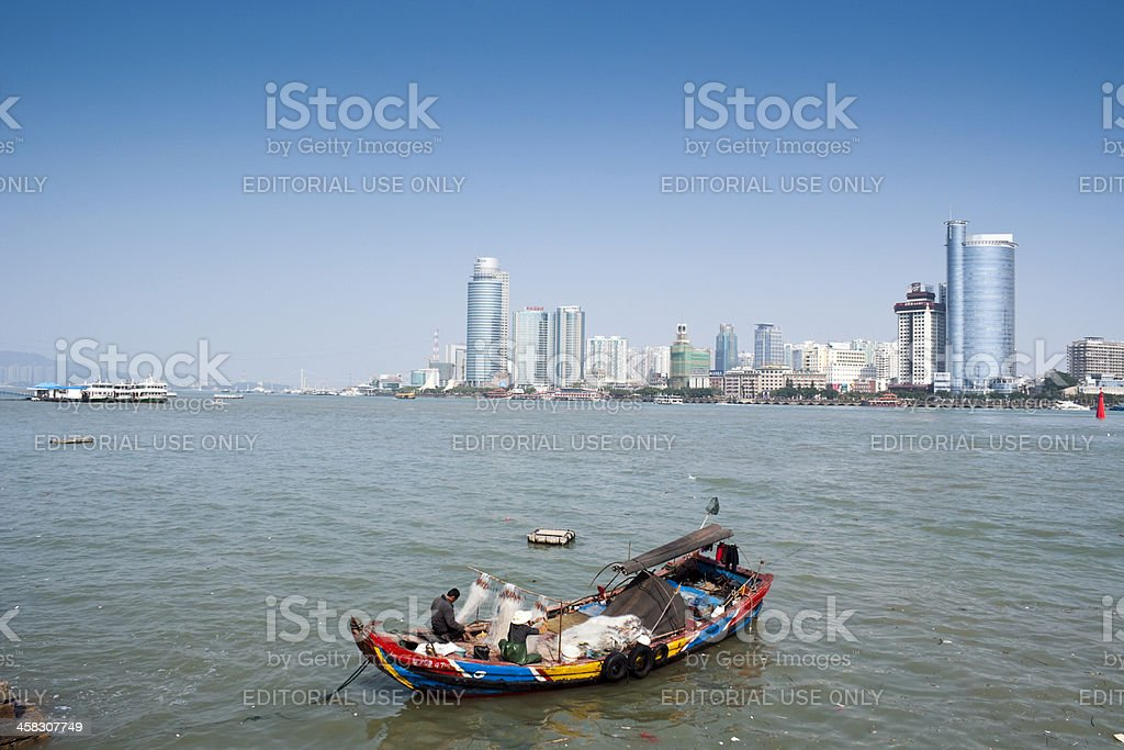 Two fishermen are mending the fishing net in small boat stock photo