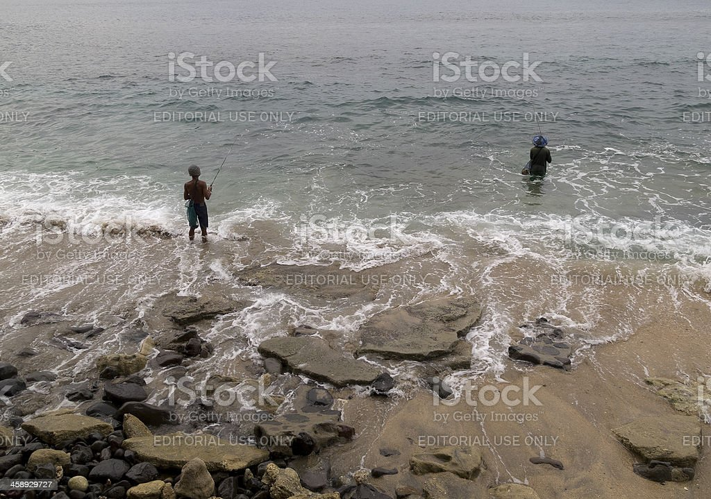 two fishermen in Lombok casting from shoreline royalty-free stock photo