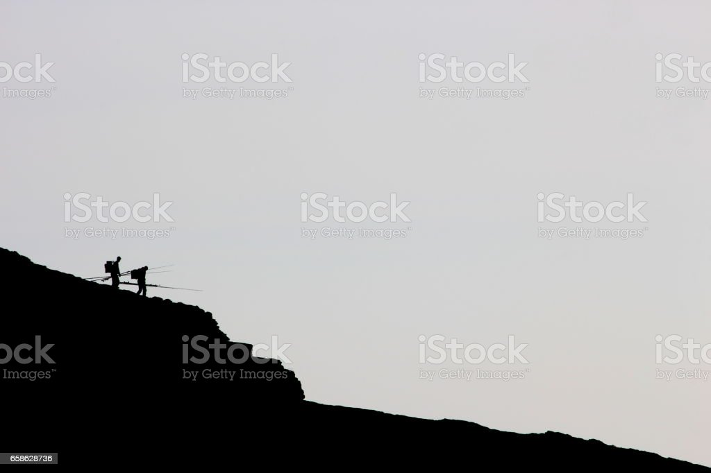 Two fishermen silhouetted on a cliff stock photo