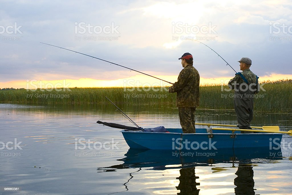 Two fishermen with fishing rods in small boat stock photo