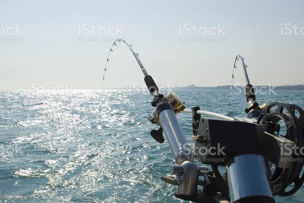 Two Fishing Pole Rods and Reels Over Turquoise Water royalty-free stock photo