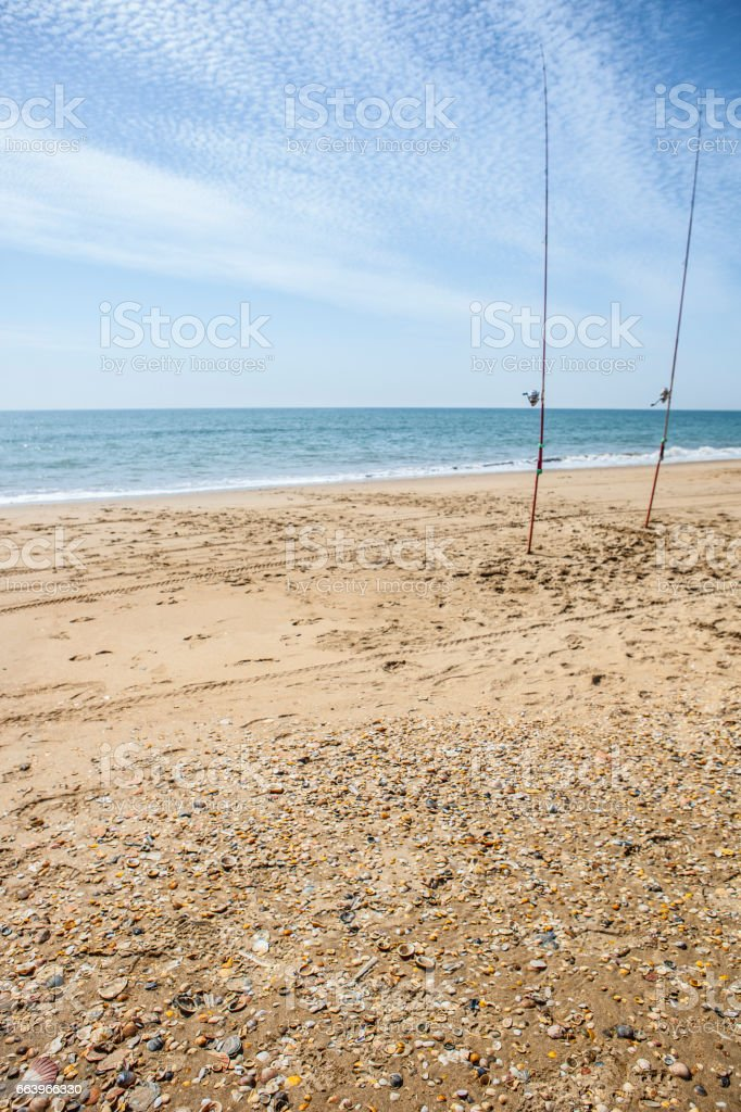 Two fishing rods hammered on the beach sand stock photo