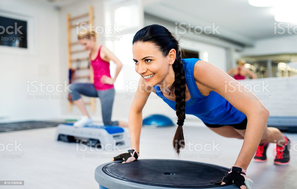 Two fit attractive women in gym doing various exercises stock photo