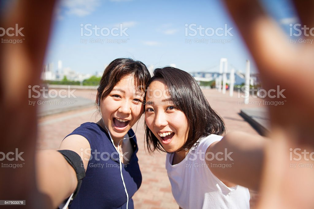 Two fit woman hold a camera and take a selfie stock photo