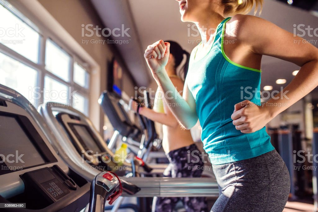 Two fit women running on treadmills in modern gym stock photo