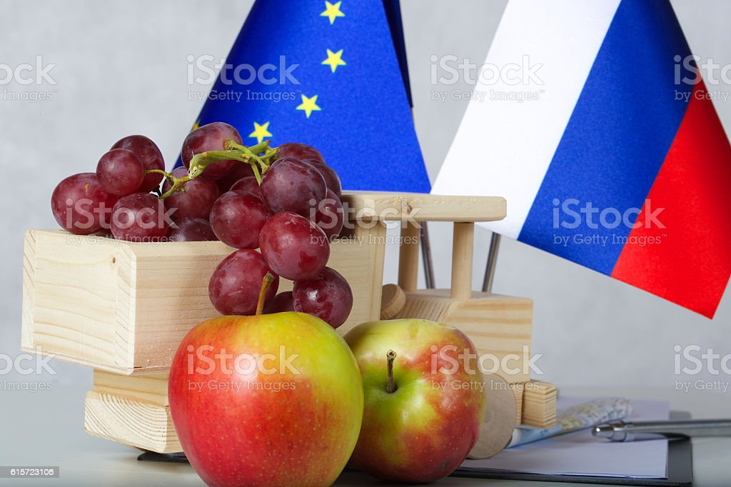 Two flags of the EU and Russia close to fruits stock photo