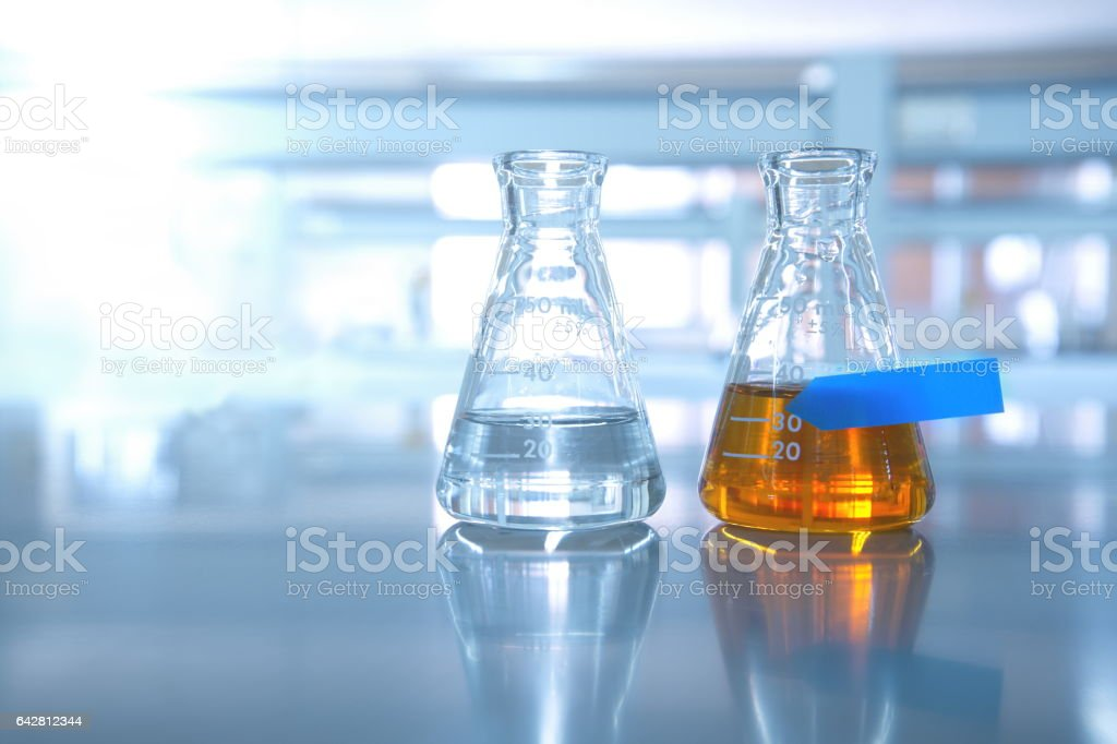 two flask with water and orange solution with blue labelscience stock photo