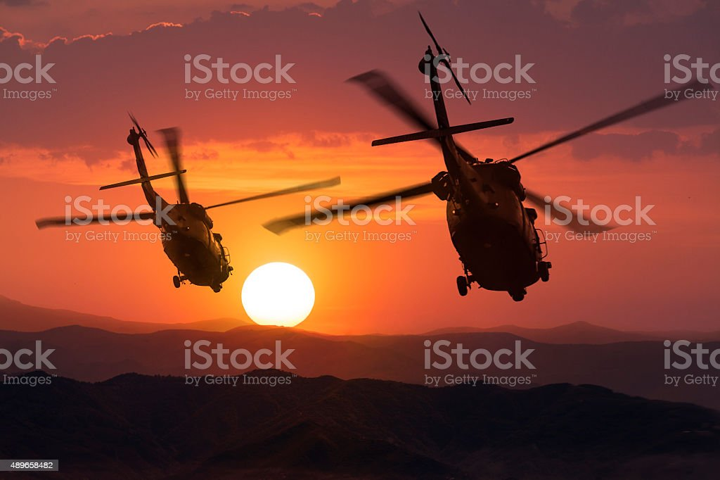 Two flying army helicopters on sunset background stock photo