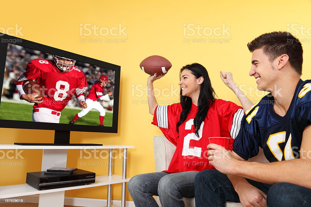 Two football fans cheering on a game while they watch on TV stock photo
