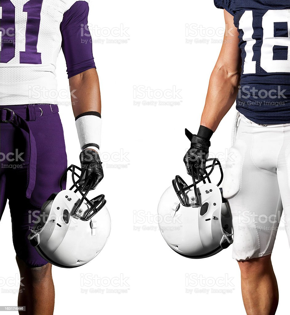 Two football players holding their helmets stock photo