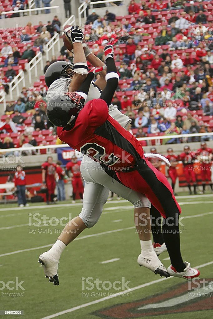 Two Football Players Jump Stretch for Airborne Ball stock photo