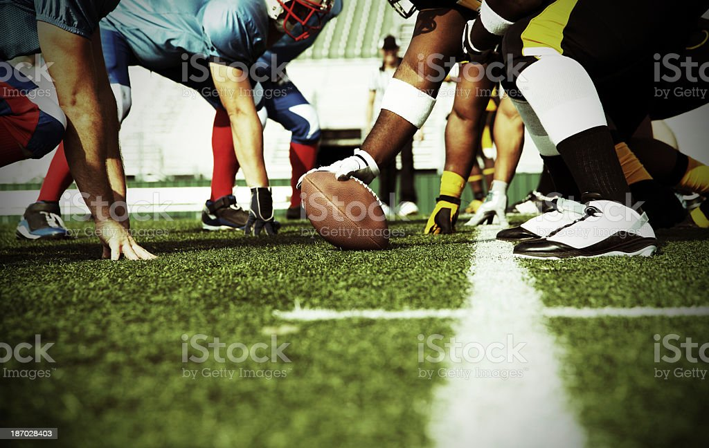 The blue, red, and white football team line up at the line of...