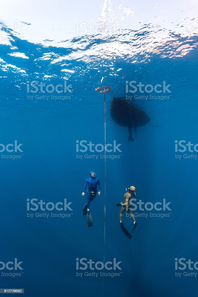 Two free divers swim under the water stock photo