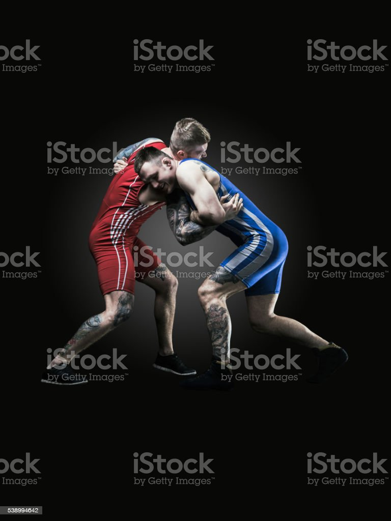 Two freestyle wrestlers in uniform wrestling on black background stock photo