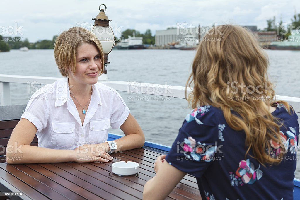 Two frendly talking girls at cafe table royalty-free stock photo