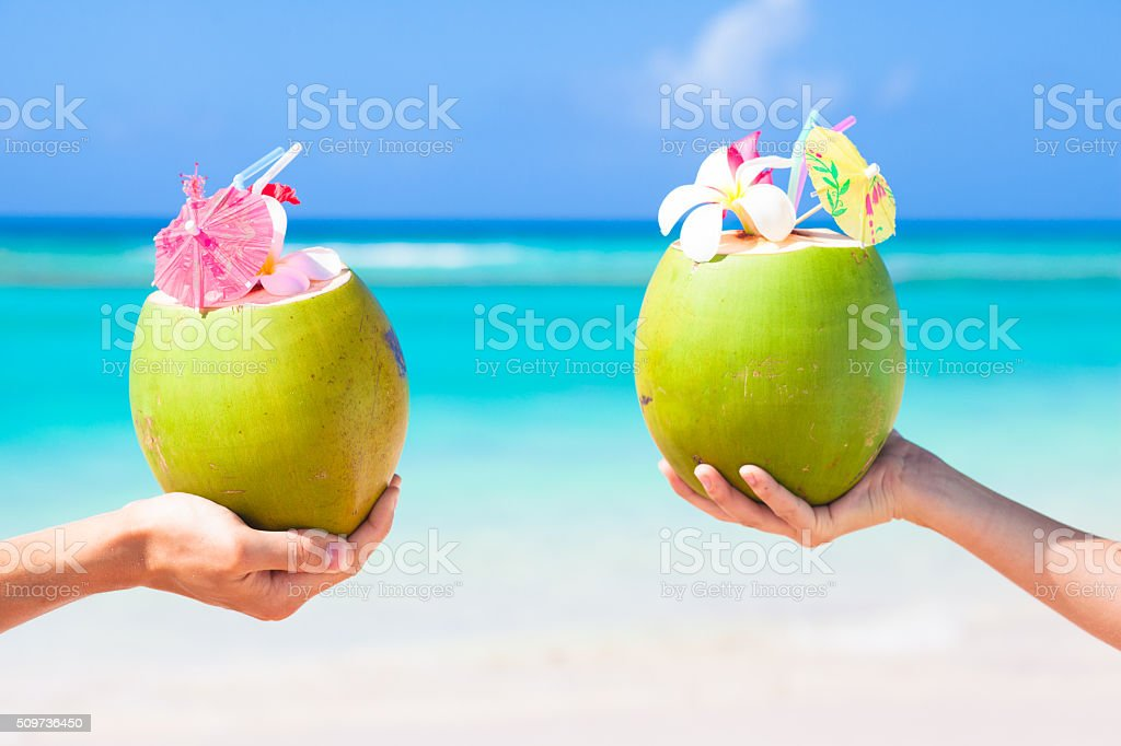 Two fresh coconut cocktails with umbrellas in hands stock photo