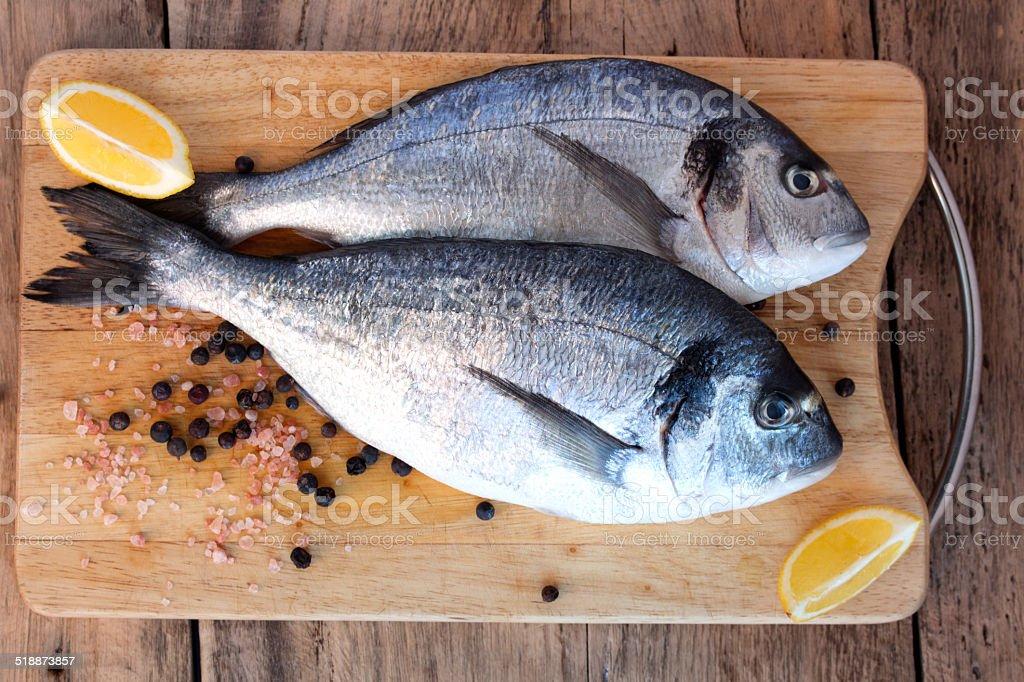 Two fresh gilt-head bream fish on cutting board stock photo