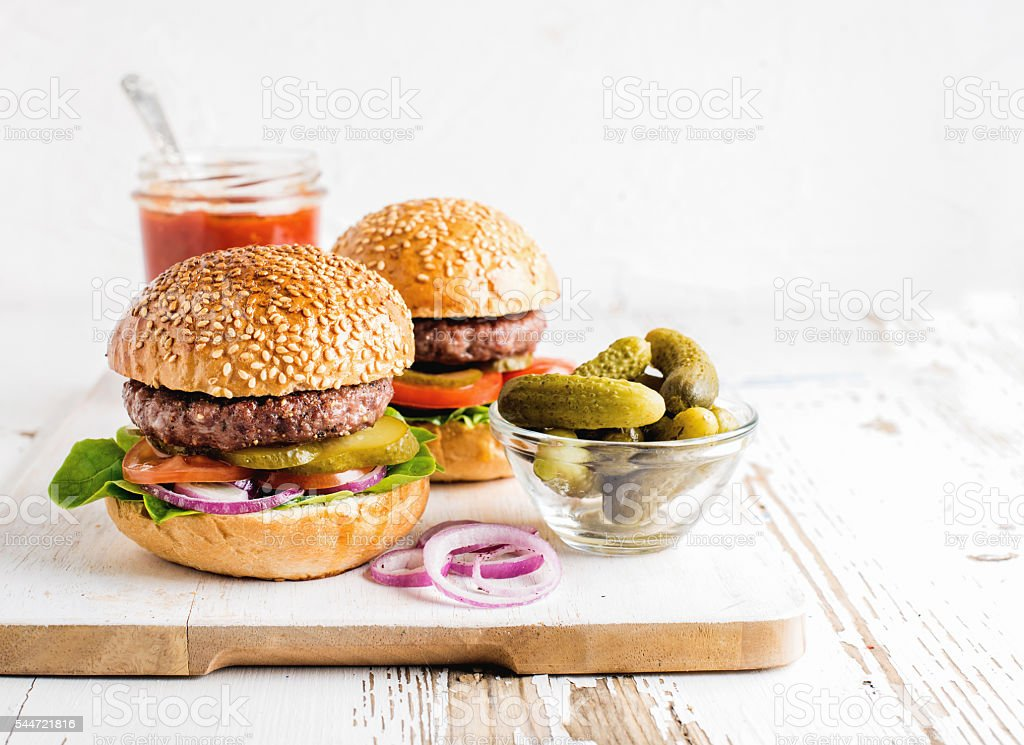 Two fresh homemade burgers, pickles, ketchup and onion rings on stock photo