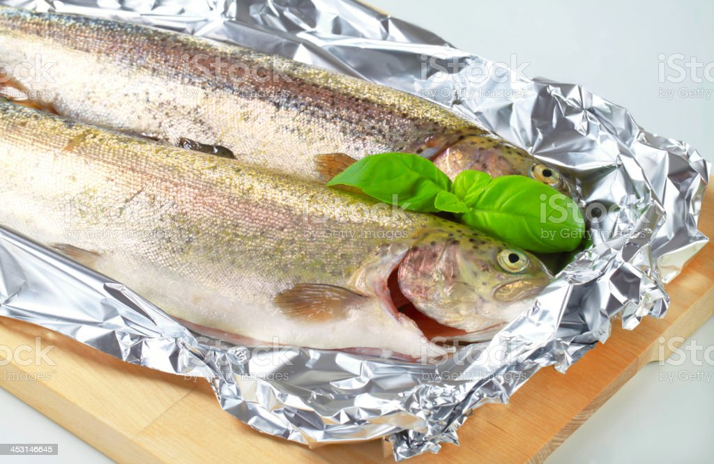 Two fresh trout on tin foil royalty-free stock photo