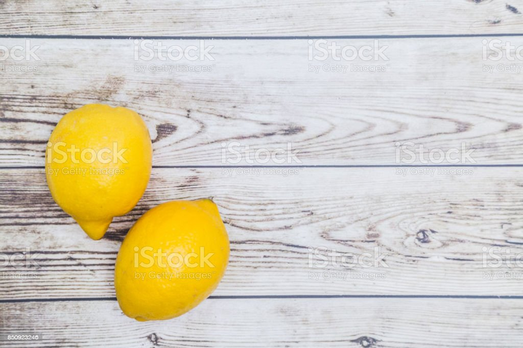 Two fresh yellow lemons on wooden background stock photo