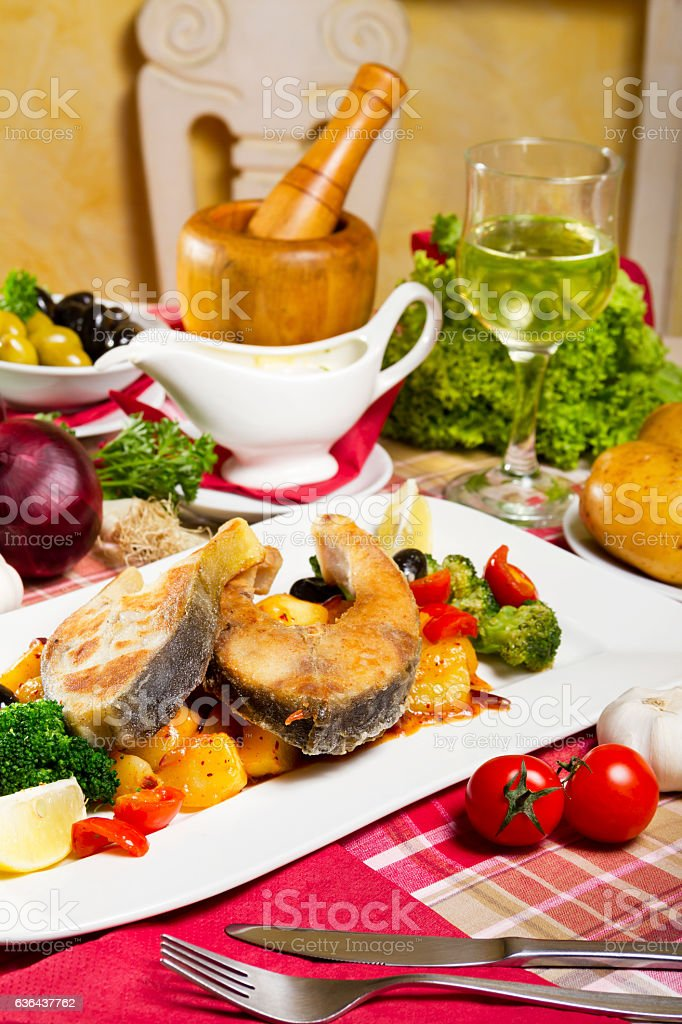 Two Fried Carp Steaks Sauce and Glass of White Wine stock photo