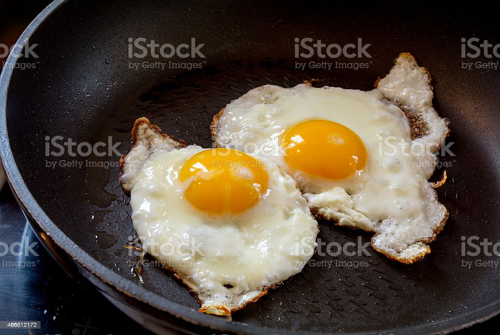 two fried eggs in a black pan stock photo
