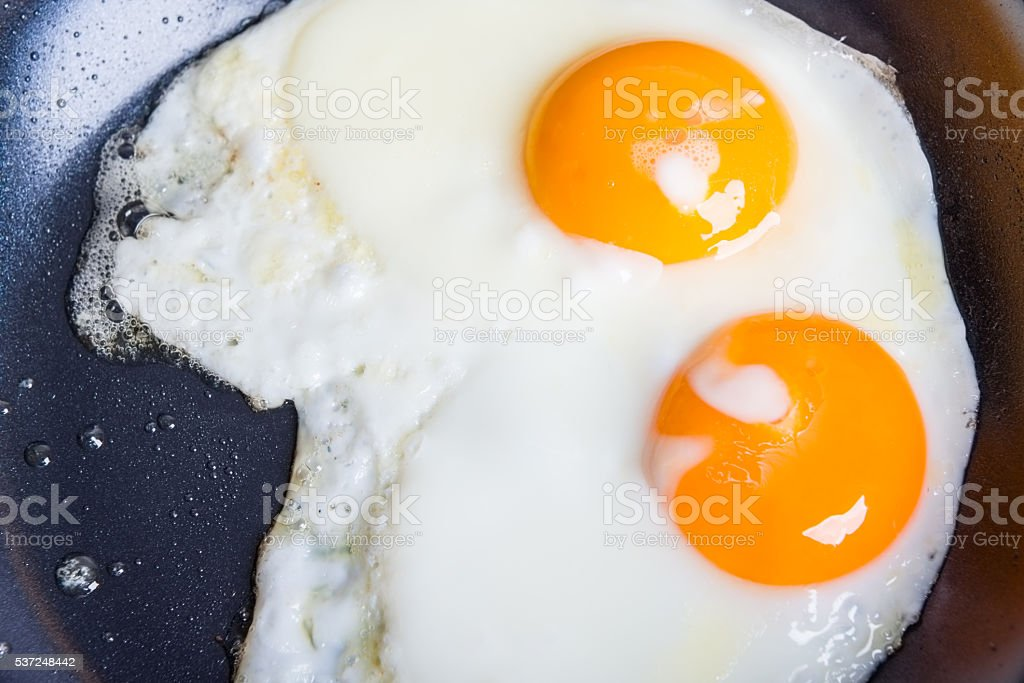 two fried eggs in a pan stock photo