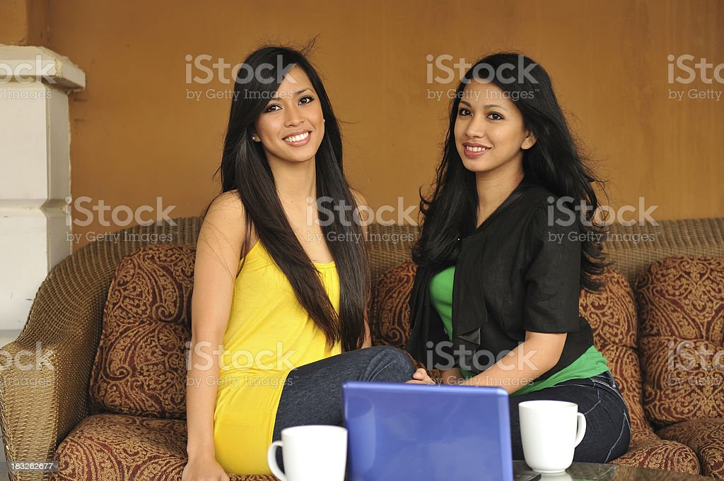 Two friends chatting and having coffee at a patio outdoors stock photo