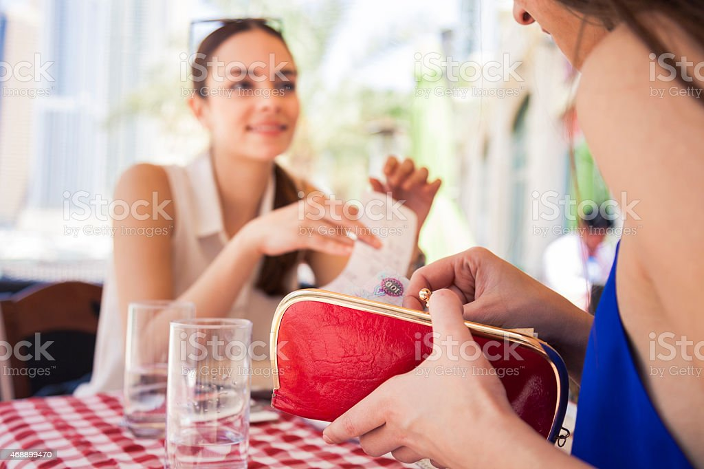 Two friends collecting money to paying in a restaurant stock photo