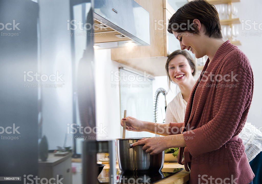 Two friends cooking a meal together stock photo