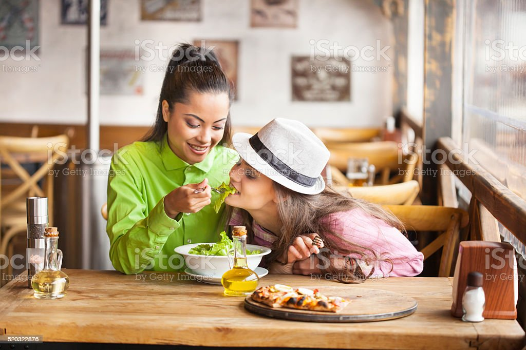 Two friends eating salad at restaurant stock photo