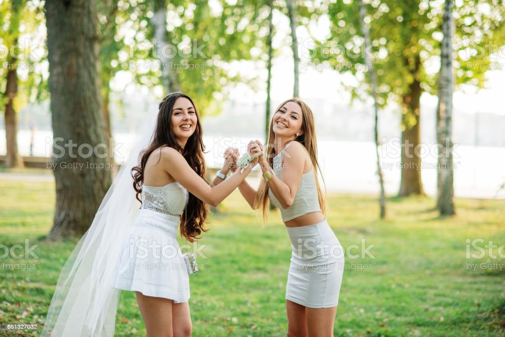 Two friends girls having fun on park at hen party. stock photo