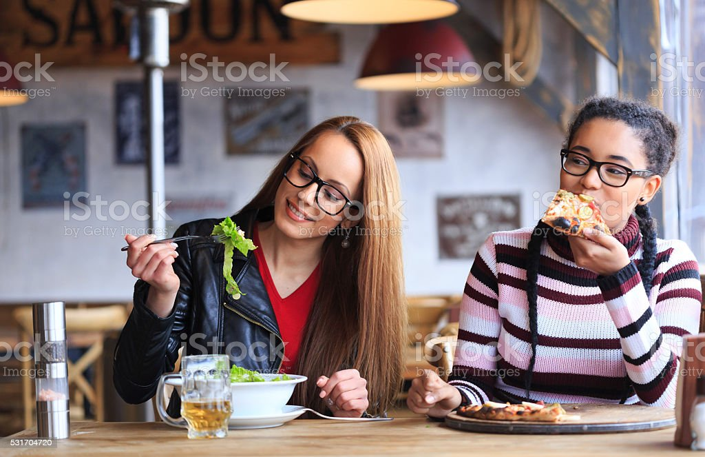 Two friends having lunch in restaurant stock photo