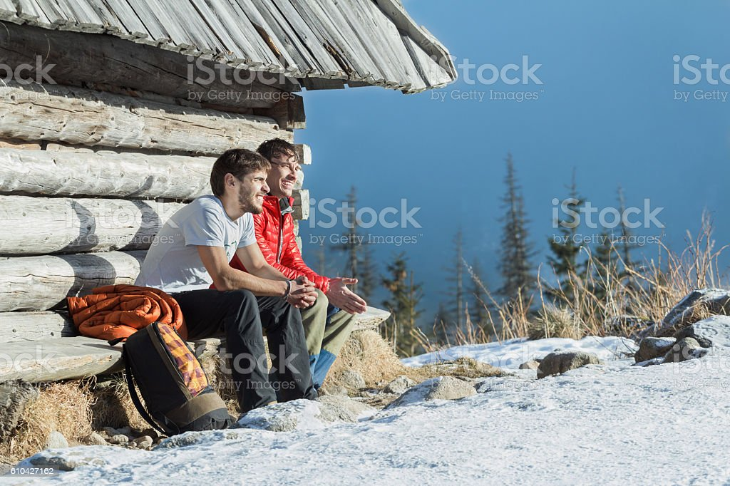 Two friends having rest on wooden bench in winter mountains stock photo