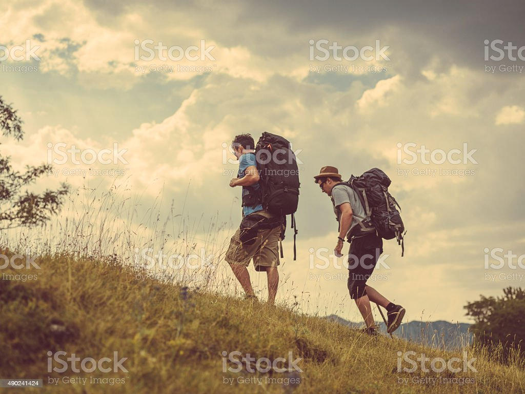 two friends hiking on hill stock photo