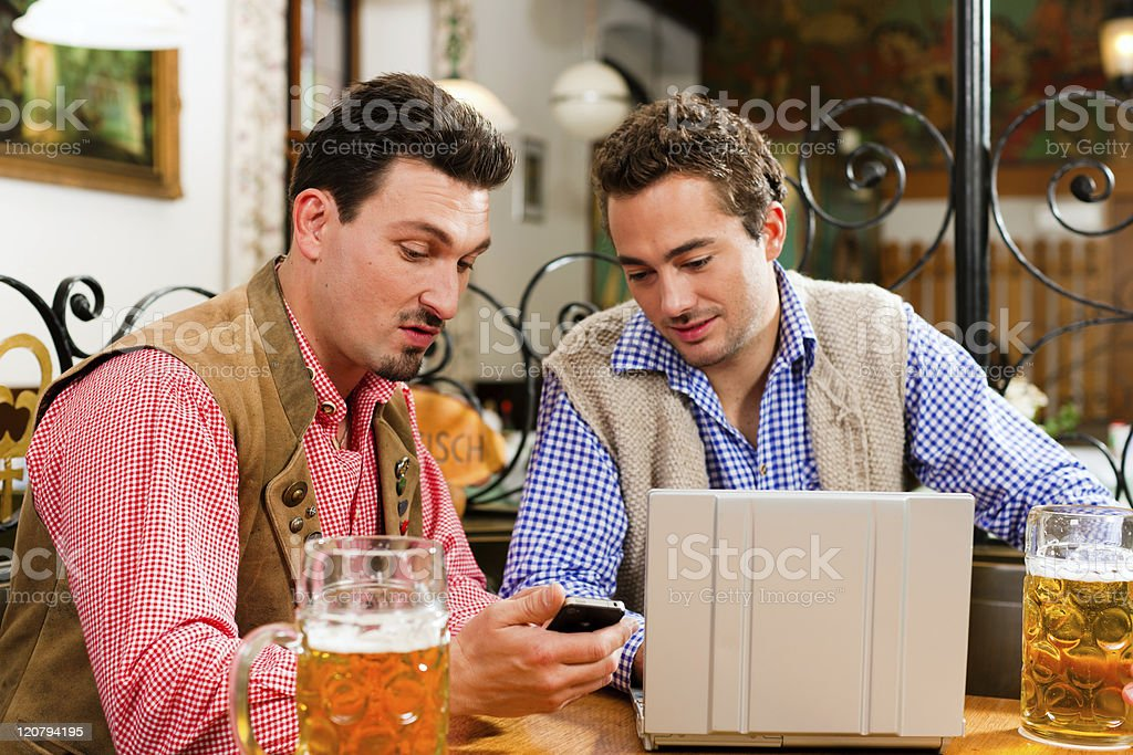 Two friends in Bavarian pub with laptop royalty-free stock photo