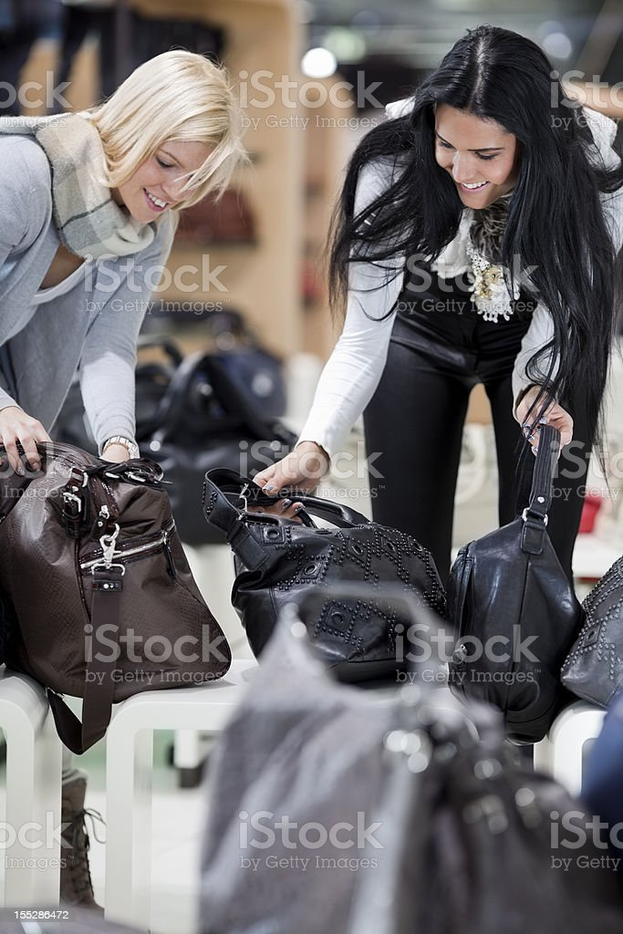 two friends  in department store looking at handbags royalty-free stock photo