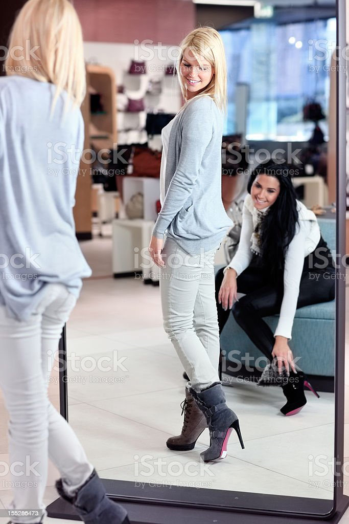 two  friends  in department store looking at new shoes stock photo
